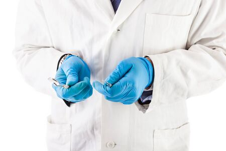 scaler: a dentist with surgical gloves and lab coat holding dental instruments