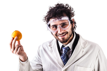 pesticides: a young researcher in lab coat holding a vibrant orange isolated over a white background