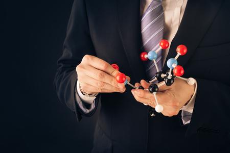 molecular model: a businessman wearing a suit and a tie holding a trinitrotoluene tnt molecular model Stock Photo