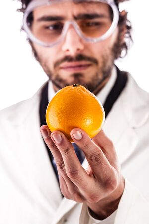 a young researcher in lab coat holding a vibrant orange isolated over a white background