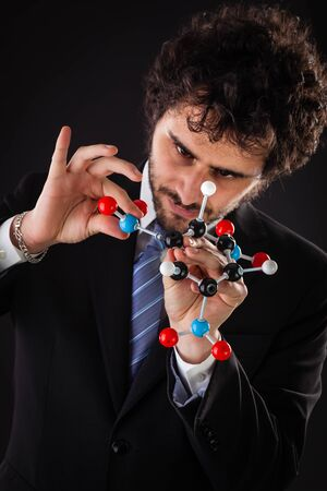 tnt: a businessman wearing a suit and a tie holding a trinitrotoluene tnt molecular model Stock Photo