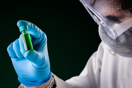 a joung and handsome doctor or researcher with a white lab coat holding a vial with green fluid