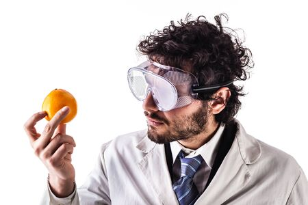 transgenic: a young researcher in lab coat holding a vibrant orange isolated over a white background