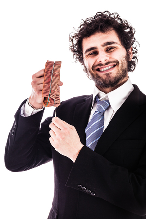 prankster: a young and handsome businessman lighting a chain firecracker isolated over a white background
