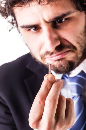 crestfallen: a young and handsome businessman with a tiny red firecracker Stock Photo