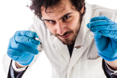 scaler: a young and handsome dentist with surgical gloves and lab coat holding dental instruments isolated over white