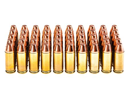 a lot of 9mm handgun bullets geometrically placed in rows isolated over a white background
