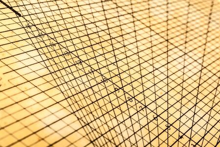 plotting: a weathered and yellowed geometrical or mathematical grid for calculations