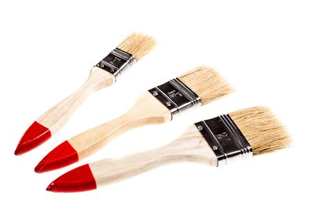 paintbrushes: three wide wooden paintbrushes isolated over a white background