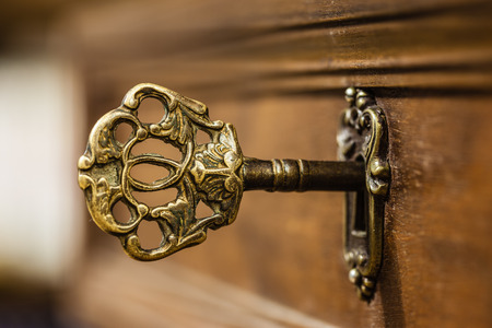 key cabinet: macro shot of an antique and weathered vintage key in his keyhole Stock Photo