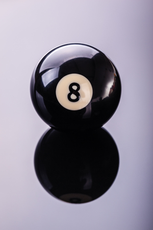 bola ocho: a pool black eight ball shot over a dark reflective surface