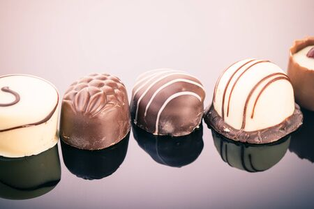 praline: a row of delicious chocolate praline shot over a dark reflective surface Stock Photo