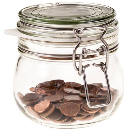 thrifty: a transparent glass jar filled with euro money isolated over a white background