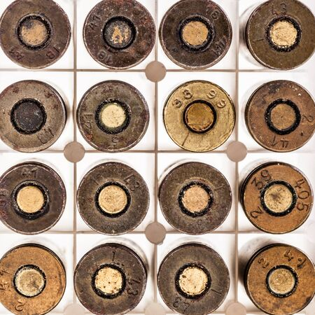 a lot of old handgun pistol bullets ammo isolated over a white background