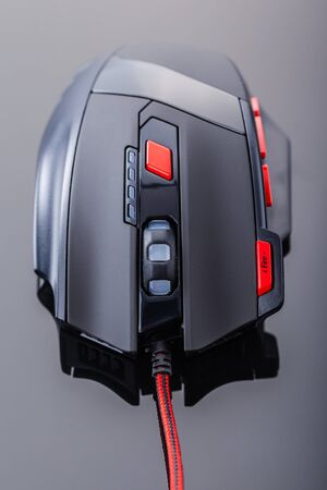 scrollwheel: a sleek modern gaming mouse with red buttons over a dark shiny surface Stock Photo