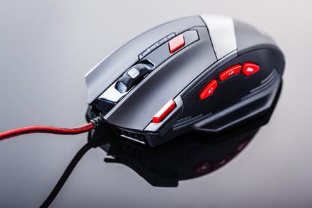 een strakke moderne gaming muis met rode knoppen op een donkere glanzende oppervlak Stockfoto