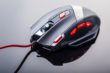 a sleek modern gaming mouse with red buttons over a dark shiny surface Archivio Fotografico