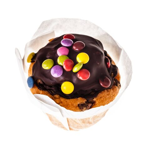 a chocolate muffin topped with smarties isolated over a white background Stock Photo