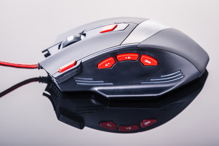 sleek: a sleek modern gaming mouse with red buttons over a dark shiny surface Stock Photo