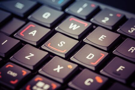 close up shot of a sleek black gaming keyboard with the wasd keys underlined over a shiny surface