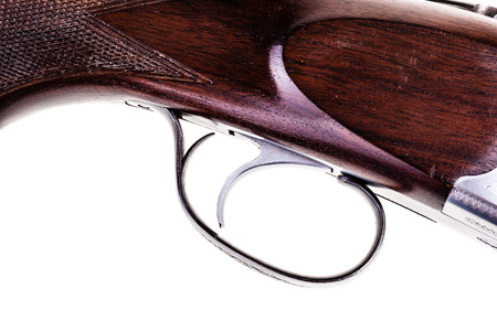 detail of the trigger of a shotgun isolated over a white background
