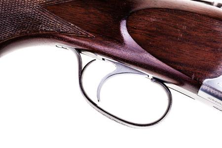 gatillo: detalle del gatillo de una escopeta aislada sobre un fondo blanco