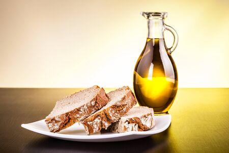 cruet: a glass cruet filled with olive oil and a loaf of bread on a dark wooden surface Stock Photo