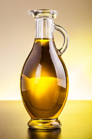 cruet: a glass cruet filled with olive oil on a dark wooden surface Stock Photo
