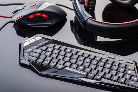 a gaming keyboard, mouse and headset shot over a dark reflective surface Фото со стока - 62889997
