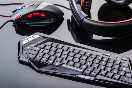 een gaming toetsenbord, muis en headset shot over een donkere reflecterend oppervlak
