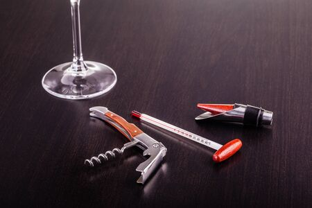 bar tool set: a glass of wine and some wine tools on a dark wooden surface Stock Photo