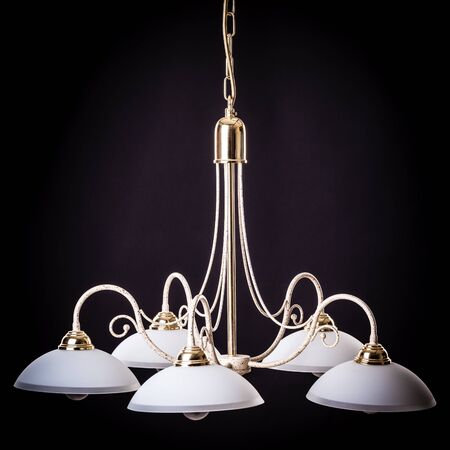 electric fixture: an old and dusty deco chandelier shot on a dark background