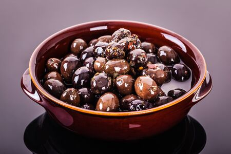 greek pot: a bowl of black and brown preserved olives shot on a dark reflective surface