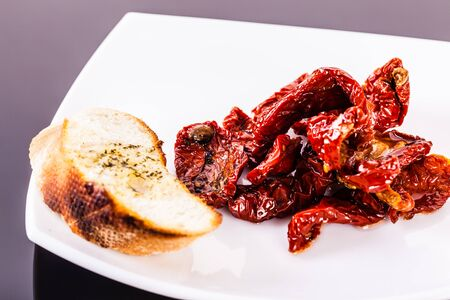 dried tomatoes on a modern plate shot on a black reflective surface Stock Photo