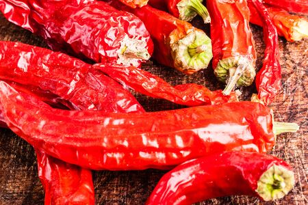 capsaicin: a bunch of red hot chili peppers on an old and scratched cutting board