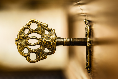 macro shot of an antique and weathered vintage key in his keyhole Stock Photo