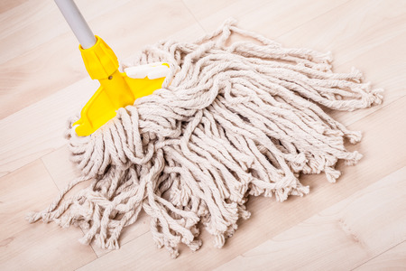 a spaghetti mop head cleaning a light wooden floor