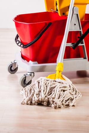Ein professioneller Moppeimer auf einem hellen Holzboden Standard-Bild - 73597630