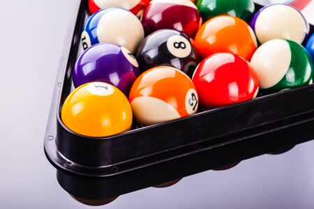 some pool balls in the triangle shot over a dark reflective surface