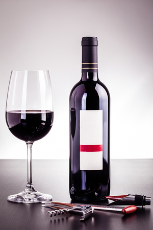 a blank labeled bottle of wine and a glass of wine and some wine tools on a dark wooden surface Banco de Imagens - 73598568