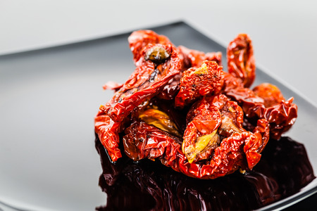 sleek: dried tomatoes on a modern plate shot on a black reflective surface Stock Photo