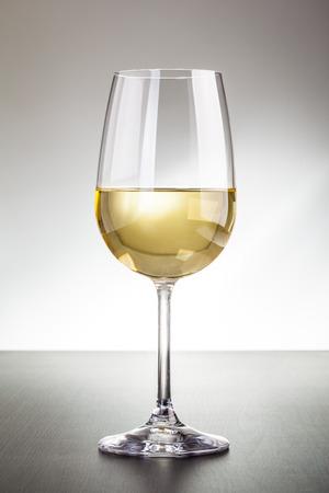 Ein Glas Rotwein auf einer hölzernen Oberfläche gegen einen getönten Hintergrund Standard-Bild - 73266847