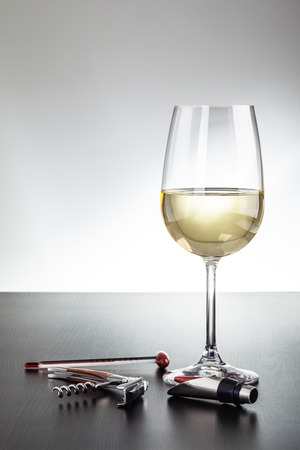 a glass of wine and some wine tools on a dark wooden surface Banco de Imagens