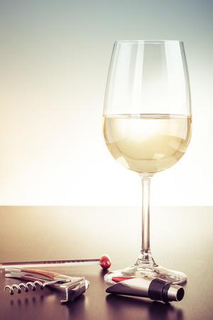 Ein Glas Wein und ein paar Wein Werkzeuge auf einem dunklen Holzoberfläche Standard-Bild - 73247336