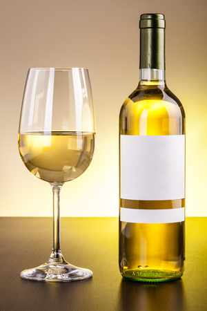 a blank labeled bottle of wine and a glass of wine on a dark wooden surface