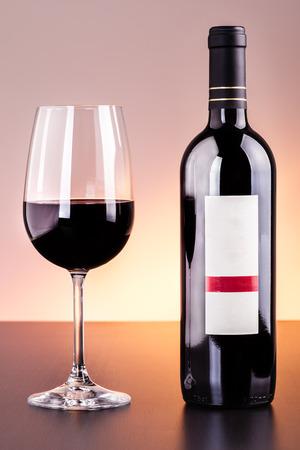Eine leere etikettierte Flasche Wein und ein Glas Wein auf einem dunklen Holzoberfläche Standard-Bild - 73598576