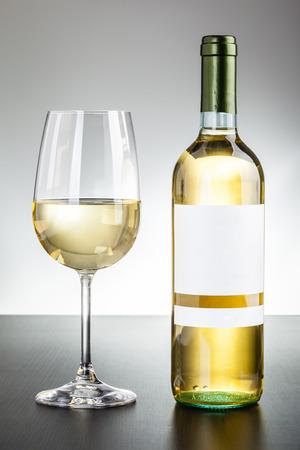 Eine leere etikettierte Flasche Wein und ein Glas Wein auf einem dunklen Holzoberfläche Standard-Bild - 73598403