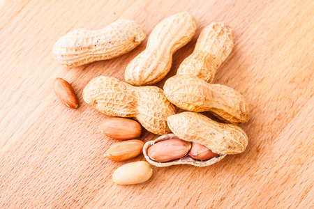 a bunch of ripe peanuts on a wooden cutting board