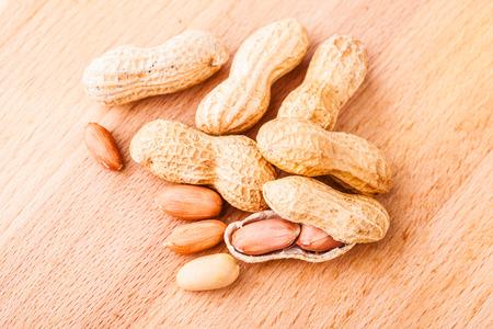 Ein paar reife Erdnüsse auf einem hölzernen Schneidebrett Standard-Bild - 73598578