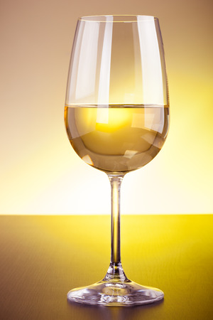 Ein Glas Rotwein auf einer hölzernen Oberfläche gegen einen getönten Hintergrund Standard-Bild - 73340347